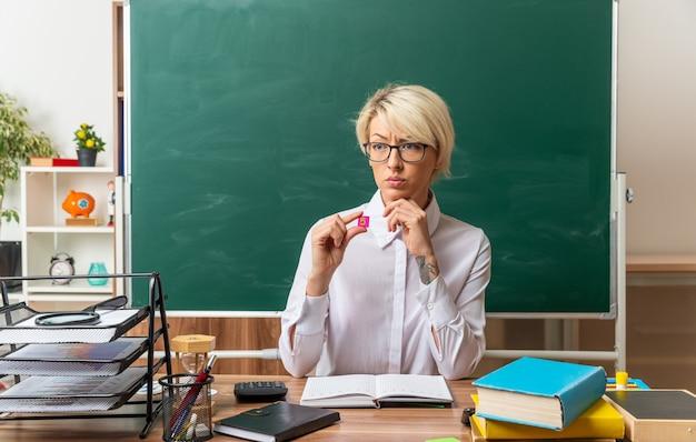 Verwirrte junge blonde lehrerin mit brille, die am schreibtisch mit schulmaterial im klassenzimmer sitzt und auf die seite schaut, die kleine quadratische nummer fünf zeigt, die die hand am kinn hält