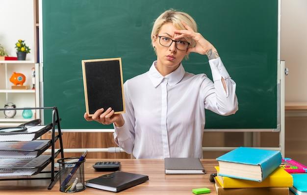 Verwirrte junge blonde lehrerin mit brille, die am schreibtisch mit schulwerkzeugen im klassenzimmer sitzt und eine mini-tafel zeigt, die die hand auf dem kopf hält