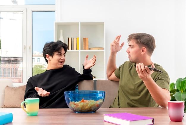 Verwirrte junge blonde und brünette gutaussehende männer sitzen mit erhobenen händen am tisch und schauen sich an. blonder mann hält telefon