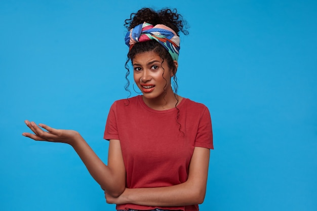 Verwirrte junge braunäugige brünette lockige dame mit festlichem make-up verzog das gesicht und hob emotional die handfläche, während sie über der blauen wand stand