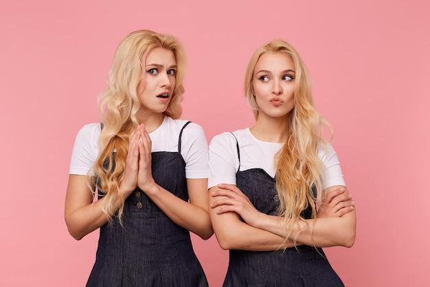 Verwirrte junge braunäugige hübsche frau mit welligem haar, die hände erhoben hält, während sie verwirrt in die kamera schaut und mit ihrer hübschen blonden unzufriedenen schwester über rosa hintergrund steht