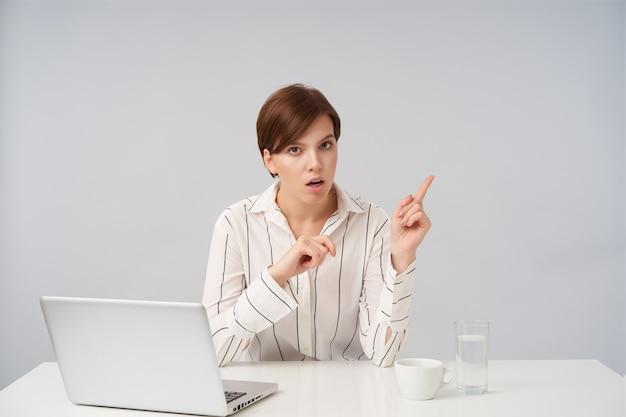 Verwirrte junge braunäugige kurzhaarige dame mit natürlichem make-up, das mit zeigefingern mit verwirrtem gesicht beiseite zeigt, isoliert auf weiß