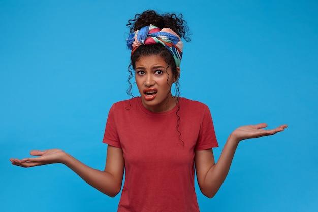 Verwirrte junge braunäugige lockige frau mit mehrfarbigem stirnband, die die handflächen hochhält und verwirrt das gesicht verzieht, während sie über der blauen wand posiert