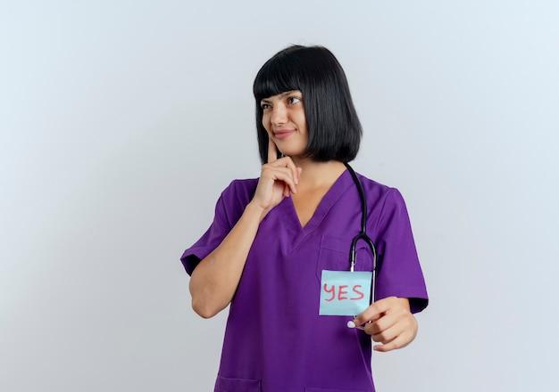 Verwirrte junge brünette ärztin in uniform mit stethoskop legt hand auf kinn und hält ja-notiz zur seite schauend