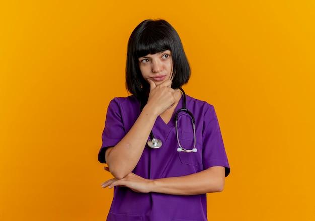 Verwirrte junge brünette ärztin in uniform mit stethoskop legt hand auf kinn und schaut zur seite