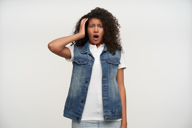 Verwirrte junge brünette dame mit dunkler haut, die die handfläche auf dem kopf hält und die augen rundet, während sie auf weißen, stirnrunzelnden augenbrauen mit geöffnetem mund posiert