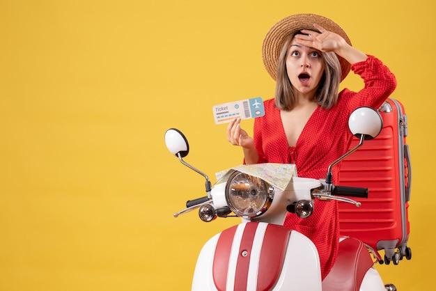Verwirrte junge dame im roten kleid, die ein ticket hält und sich die hand auf die stirn legt, auf dem moped