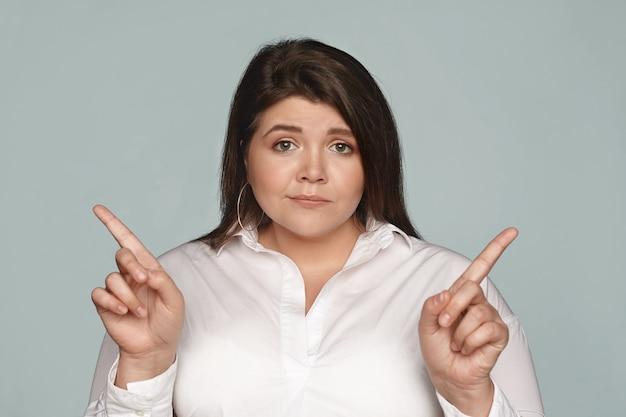 Verwirrte junge dunkelhaarige geschäftsfrau mit pausbäckigen wangen und kurvigem körper, die ihre zeigefinger in entgegengesetzte richtungen zeigt, kann sich nicht zwischen zwei geschäftskonzepten entscheiden, die zweifelhaft aussehen