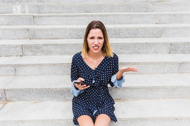 Verwirrte junge frau, die auf dem treppenhaus hält smartphone sitzt