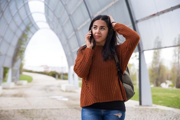 Verwirrte junge frau, die auf mobiltelefon spricht