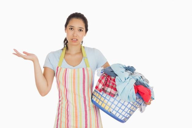 Verwirrte junge frau, die den wäschekorb voll der schmutzigen wäscherei hält