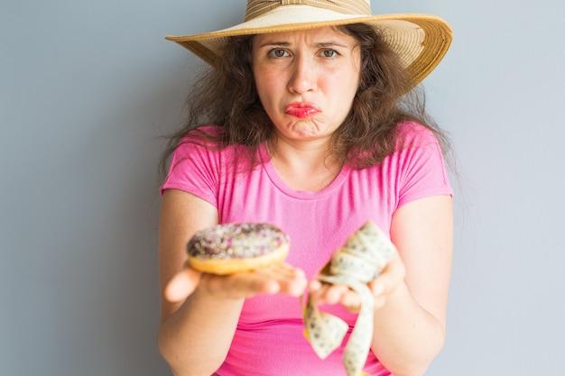 Verwirrte junge frau, die einen donut und ein messendes band hält konzept von süßigkeiten, ungesundem junk food und fettleibigkeit.