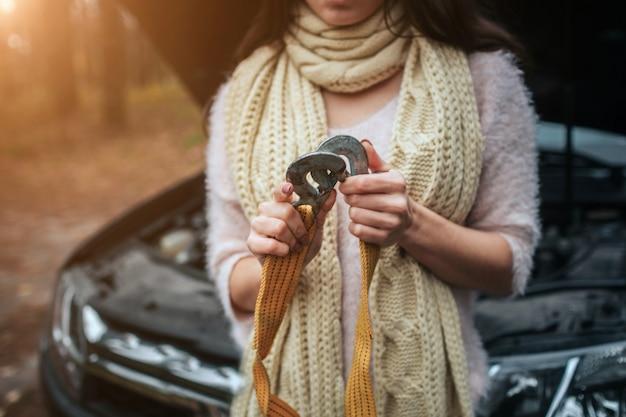 Verwirrte junge frau, die kaputte automotorreparatur auf der straße betrachtet