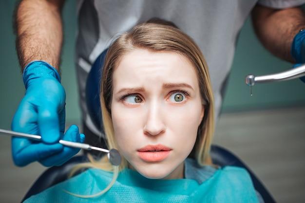 Verwirrte junge frau sitzen auf stuhl in der zahnmedizin. sie hält die augen verdreht. zahnarzt steht hinter ihr und hält werkzeuge für die zahnbehandlung.