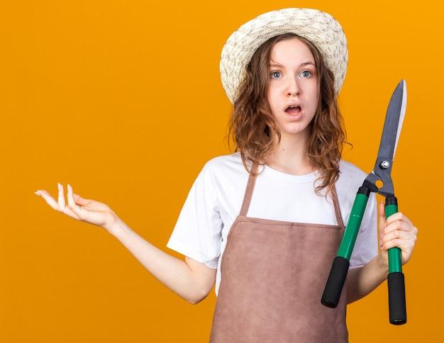 Verwirrte junge gärtnerin mit gartenhut, die eine auf orangefarbene wand isolierte, ausbreitende hand der gartenschere hält