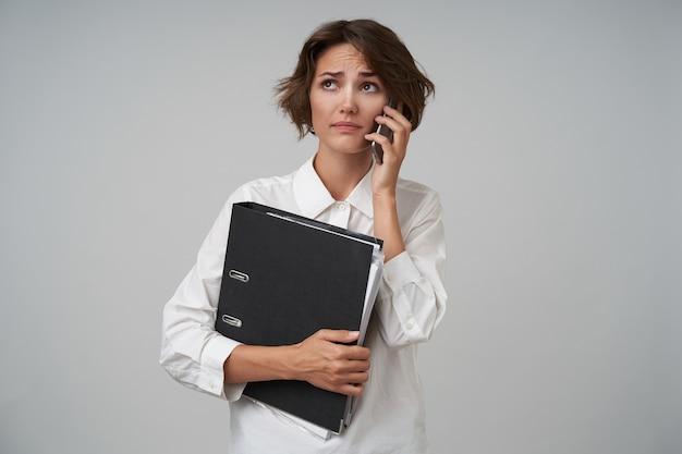 Verwirrte junge hübsche frau mit lässiger frisur, die als sekretärin arbeitet und ihren chef anruft, dokumente für geschäftstreffen vorbereitet, weißes hemd tragend