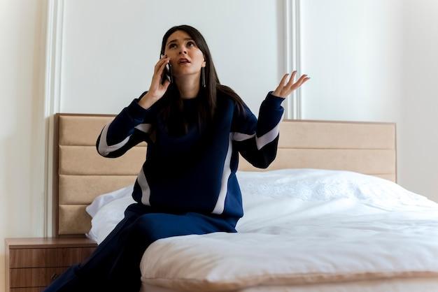 Verwirrte junge hübsche kaukasische frau, die auf dem bett im schlafzimmer sitzt und am telefon spricht und leere hand zeigt