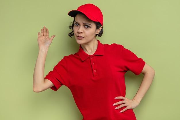 Verwirrte junge hübsche lieferfrau, die mit erhobener hand steht