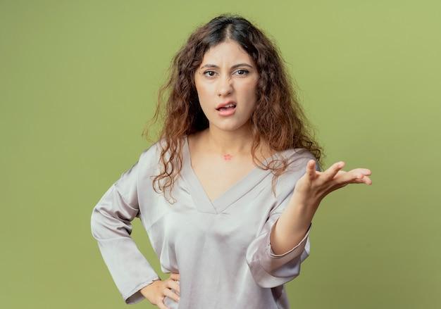 Verwirrte junge hübsche weibliche büroangestellte, die hand heraushält und hand auf hüfte lokalisiert auf olivgrüner wand setzt