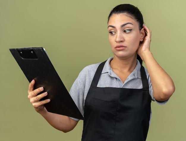 Verwirrte junge kaukasische friseurin in uniform mit zwischenablage, die den kopf einzeln auf olivgrüner wand berührt