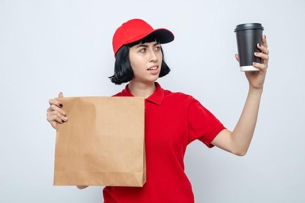 Verwirrte junge kaukasische lieferfrau, die lebensmittelpaket hält und pappbecher anschaut