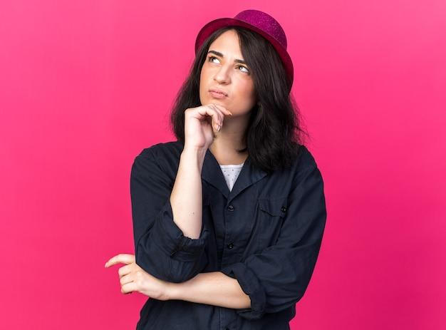 Verwirrte junge kaukasische partyfrau mit partyhut, die nach oben schaut und die hand am kinn hält, isoliert auf rosa wand