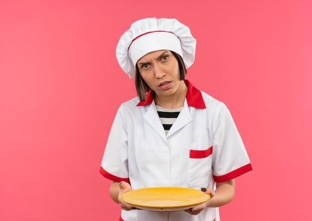 Verwirrte junge köchin in der kochuniform, die leere platte lokalisiert auf rosa mit kopienraum hält