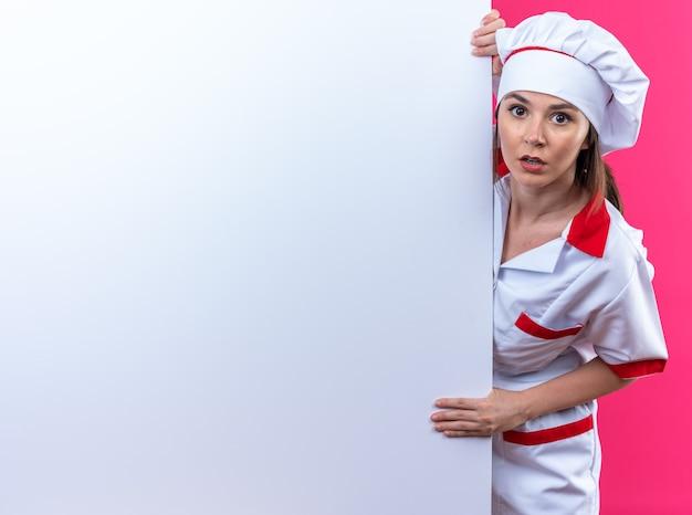 Verwirrte junge köchin in kochuniform, die hinter weißer wand steht, isoliert auf rosa hintergrund mit kopierraum copy