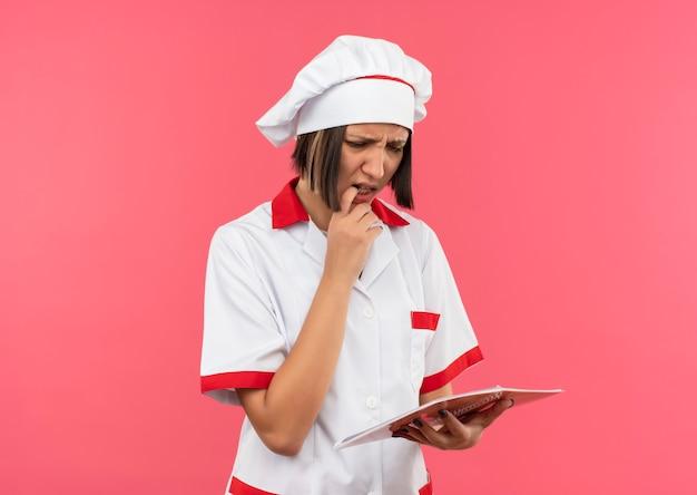 Verwirrte junge köchin in kochuniform, die notizblock mit finger auf lippe hält und auf rosa mit kopienraum isoliert betrachtet