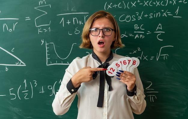 Verwirrte junge lehrerin mit brille, die vor der tafel steht und auf nummernfächer im klassenzimmer zeigt