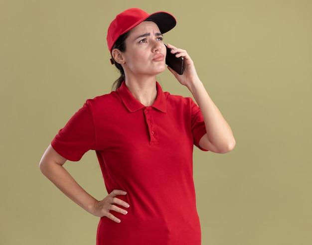 Verwirrte junge lieferfrau in uniform und mütze, die die hand auf der taille hält und am telefon spricht und auf die seite schaut