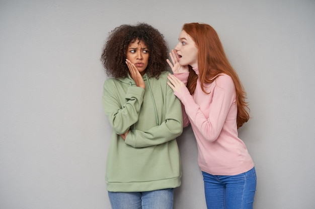 Verwirrte junge lockige dunkelhäutige brünette in grünem hoodie und jeans, die die handfläche auf der wange hält und verwirrt die augenbrauen runzelt, während sie eine unerwartete geschichte von ihrer freundin hört