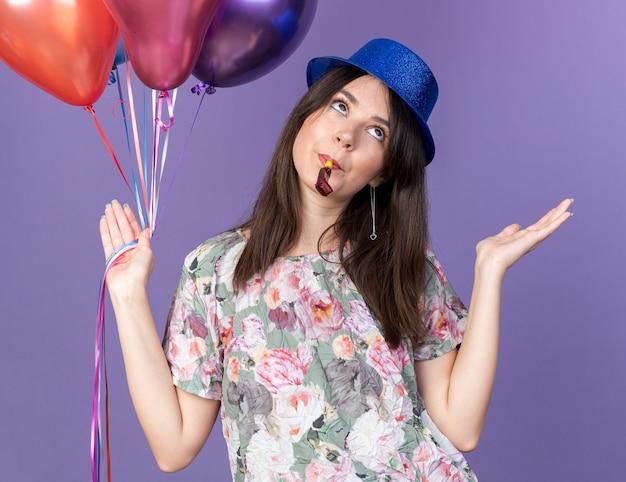Verwirrte junge schöne frau mit partyhut, die luftballons hält und die partypfeife bläst, die hände isoliert auf blauer wand ausbreitet