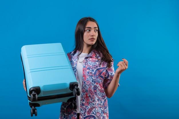Verwirrte junge schöne reisende frau, die reisekoffer hält, der mit zweifelhaftem gesichtsausdruck beiseite steht, der über isoliertem blauem raum steht