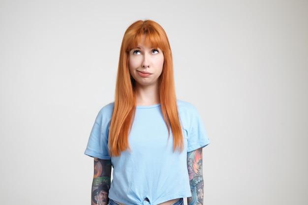 Verwirrte junge schöne rothaarige tätowierte frau mit lässiger frisur, die auf ihr haar bläst, während sie nach oben schaut und über weißem hintergrund mit den händen nach unten steht