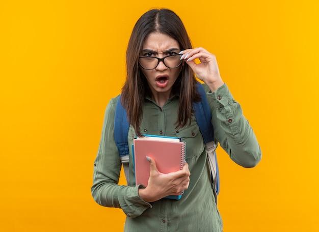 Verwirrte junge schulfrau mit rucksack mit brille, die bücher hält