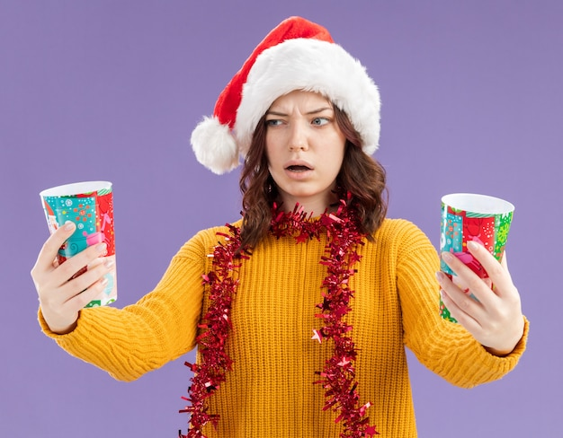 Verwirrte junge slawische mädchen mit weihnachtsmütze und mit girlande um den hals halten und betrachten pappbecher isoliert auf lila hintergrund mit kopienraum