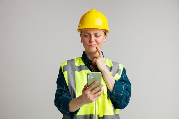 Verwirrte junge weibliche bauarbeiterin, die schutzhelm und sicherheitsweste hält und handy hält und finger auf mundwinkel hält