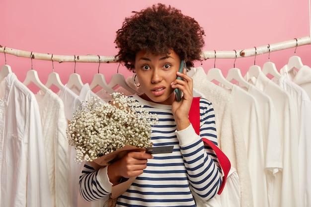 Verwirrte lockige frau telefoniert, hält handy in der nähe des ohrs, hält blumenstrauß, prüft informationen von kreditkarte