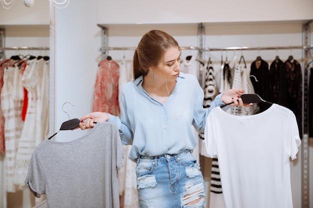 Verwirrte nachdenkliche junge frau, die zwischen zwei t-shirts im bekleidungsgeschäft wählt