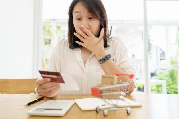 Verwirrte porträt junge frau hält kreditkarten mit problem online-zahlung