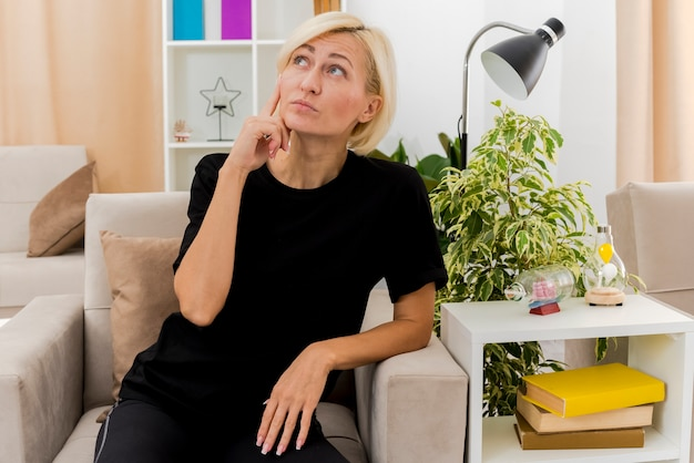 Verwirrte schöne blonde russische frau sitzt auf sessel, der hand auf kinn setzt und im wohnzimmer nach oben schaut