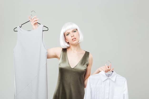 Verwirrte schöne junge frau, die zwischen hemd und kleid wählt
