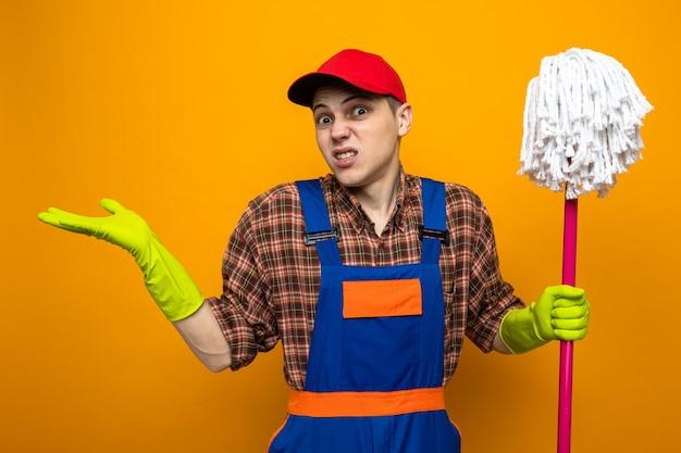 Verwirrte, sich ausbreitende hände junger putzmann in uniform und mütze mit handschuhen, die mop halten