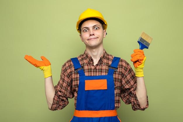Verwirrte, sich ausbreitende hand junger männlicher baumeister, der uniform mit handschuhen trägt, die pinsel halten
