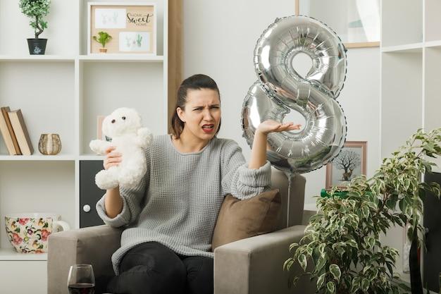 Verwirrte, sich ausbreitende hand schönes mädchen am glücklichen frauentag, der den teddybären hält, der auf einem sessel im wohnzimmer sitzt
