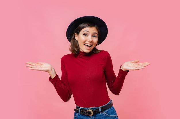 Verwirrte süße frau breitet hände mit zweifel aus, gekleidet in roten pullover, isoliert. frau steht vor dilemma, unsicher zu sein