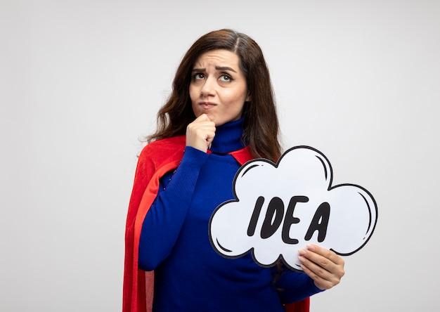 Verwirrte superfrau mit rotem umhang legt hand auf kinn und hält ideenblase, die isoliert auf weißer wand nach oben schaut