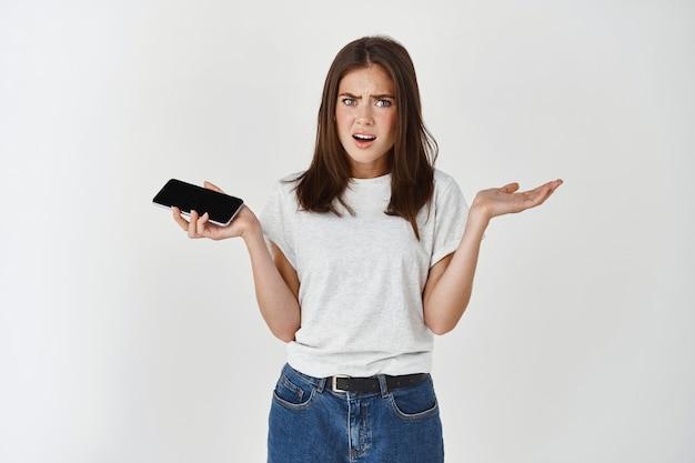 Verwirrte und enttäuschte brünette frau zuckt mit dem smartphone, schaut ahnungslos nach vorne und steht über weißer wand
