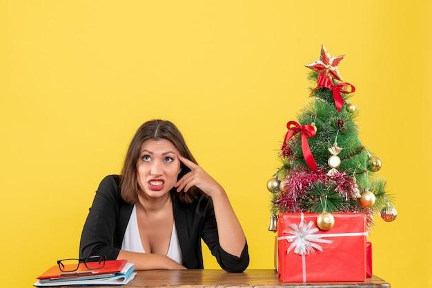 Verwirrte und nervöse junge frau, die an einem tisch nahe geschmücktem weihnachtsbaum im büro auf gelb sitzt